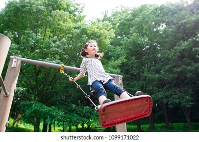 Girl playing in the swing