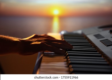 Girl playing a synthesizer at sunset