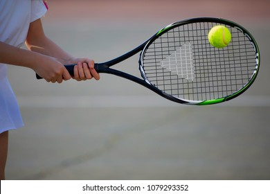 Girl playing tennis on the court on a beautiful sunny day