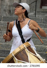 Girl playing traditional Brazilian maracatu rhythms on alfaia drum during a performance.