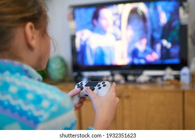 Girl playing video game with joystick at home