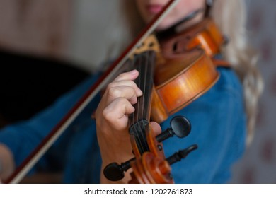 Girl playing the violin. Hand of a girl and a fiddle. Close-up portrait