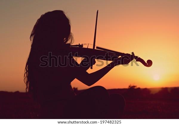 夕方にバイオリンを弾く女の子