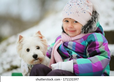 girl playing with a white dog winter snow happiness