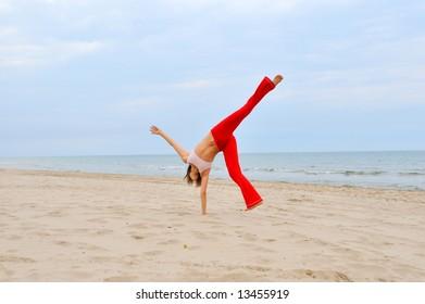 girl playing/doing gymnastics on the beach