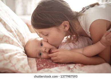 The girl plays with the baby, kisses the little sister on the bed in the bedroom, life style in pink color