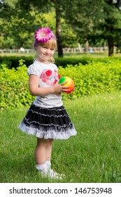 girl plays with ball on the nature