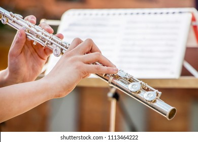 The girl plays the flute. Flute in the hands of the musician during the performance of the musical play