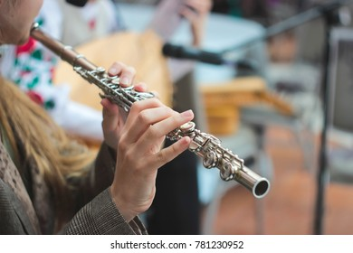 A girl plays a flute on a street concert