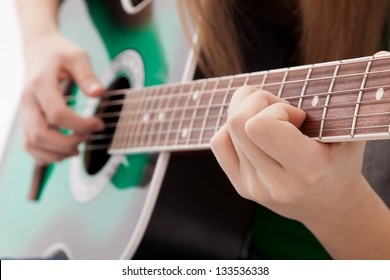 The girl plays a guitar, close-up