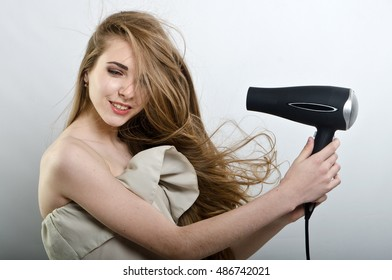 the girl plays with the hair dryer with hair fef9b55f7