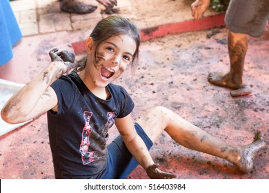 Girl plays with mud while sitting on the floor