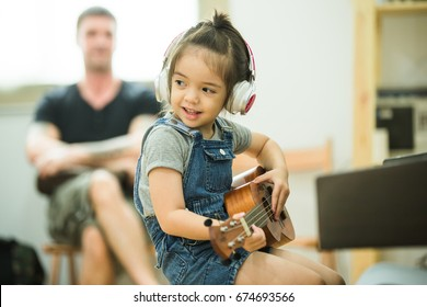 The girl plays music and her face is happy on the background with the family in the living room.