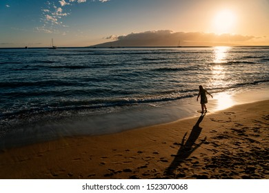 A girl plays on the beach in Lahaina, Maui, Hawaii at sunset.