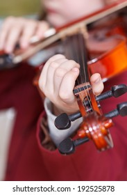 girl plays on violin - chord on fingerboard close up