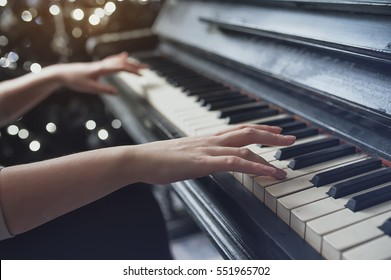 The girl plays piano, close up , white and black keyboard