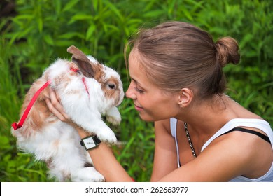 A girl plays with a rabbit on green grass.