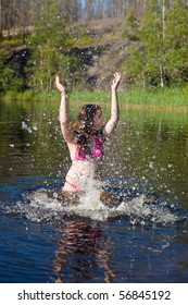 The girl plays with water in summer lake
