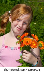Girl is plucking a bouquet of marigolds in the garden