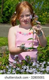 Girl is plucking flowers in the garden