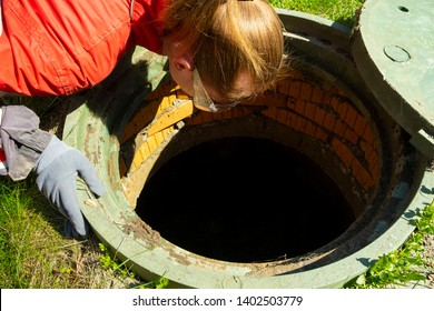 Girl plumber looks into an open draining manhole.Service of the house individual sewerage.