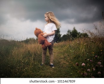 The girl with plush bear. Stormy sky, tall grass fields. The concept of children's loneliness, the character of the child