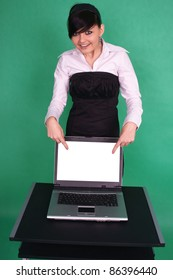 Girl pointing at blank laptop screen.