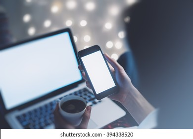 Girl pointing finger a black smartphone and using open laptop with a empty blank screen monitor and a cup of coffee or tea on the background bokeh light in a chair in a homely atmosphere