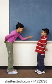 Girl pointing finger at boy in school classroom. Vertically framed shot.