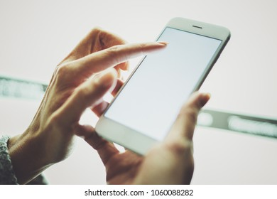 Girl pointing finger on screen smartphone.Female hands texting message mobile phone.Closeup on blurred light coloured background