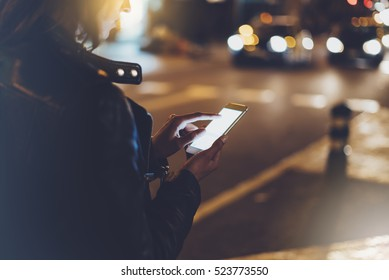 Girl pointing finger on screen smartphone on background illumination glow bokeh light in night atmospheric christmas city, hipster using mobile phone, headlights auto taxi; mockup glitter street