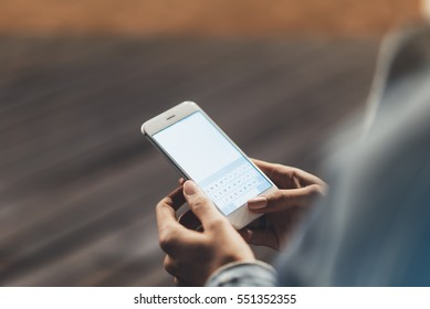 Girl pointing finger on screen smartphone on background wooden floor in night atmospheric city, hipster using in female hands and texting mobile phone, mockup glitter street lifestyle, blured backdrop