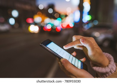 Girl pointing finger on screen smartphone on background illumination bokeh color light in night atmospheric city, using in hands texting mobile phone. Using cellphone at night