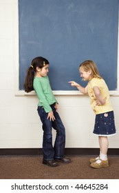 Girl pointing finger at other girl in school classroom. Vertically framed shot.