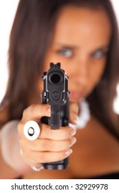 Girl pointing a gun isolated in white background. Shallow depth of field. Focus on the tip of the gun.
