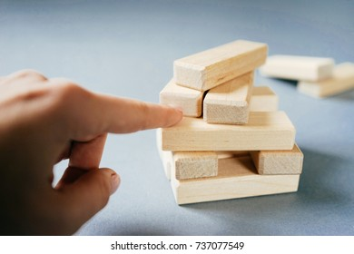 the girl points a finger at a small pile of wooden blocks