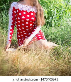 Girl in polka-dot dress reads a book in nature