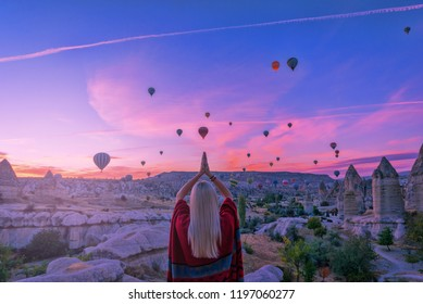 girl in a poncho at dawn in the valley of love Cappadocia looks at the balloons soaring