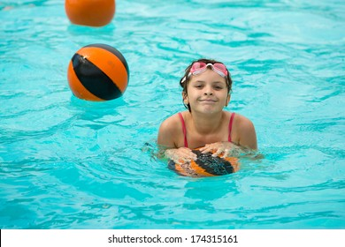 Girl in a pool playing in a turquoise water with basketball