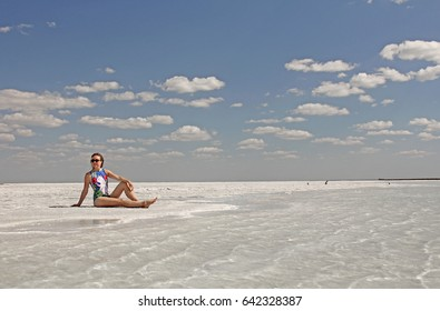 A girl with a pool swimsuit sits on the beach on white sand