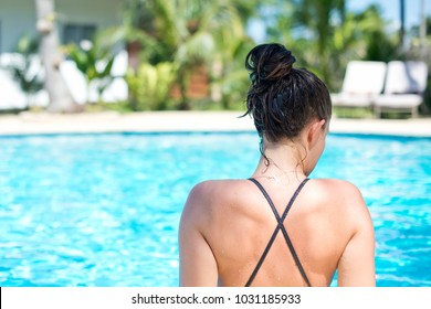 A girl at the poolside at her resort.