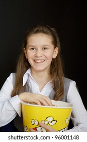 girl with popcorn on a black background