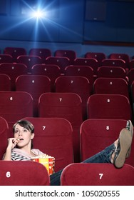 A girl with popcorn sitting alone at the cinema