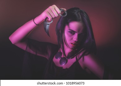 A girl portrait with a knife - karambit. Used color filters for light sources.