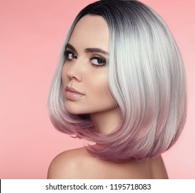 Girl Portrait of Ombre bob short hairstyle. Beautiful hair coloring woman. Trendy puprle haircut. Blond model with short shiny haircuts isolated on pink Background. Makeup. Beauty Salon.