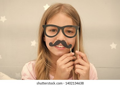 Girl pose with photo booth props glasses and mustache in bedroom. Child girl with party glasses. Child imitate masculinity or want look like her dad. Kid with mustache and eyeglasses.