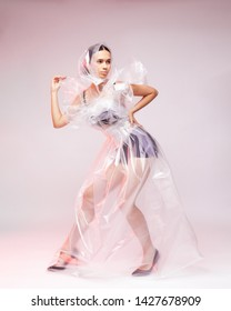 Girl posing in a dress made of plastic film. Fashion portrait.