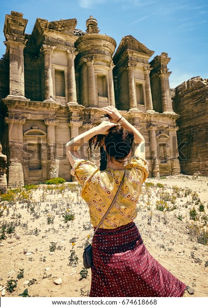 pretty nice acb49 aa29d A girl is posing in front of the monastery y of Petra in the desert of