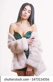 Girl posing fur coat. Female with makeup wear mink beige fur coat. Woman wear velvet sexy dress and short coat. Fashion concept. Girl elegant lady wear fashionable coat jacket. Luxurious fur.