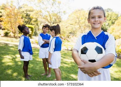 Girl posing with her soccer team in the background in park